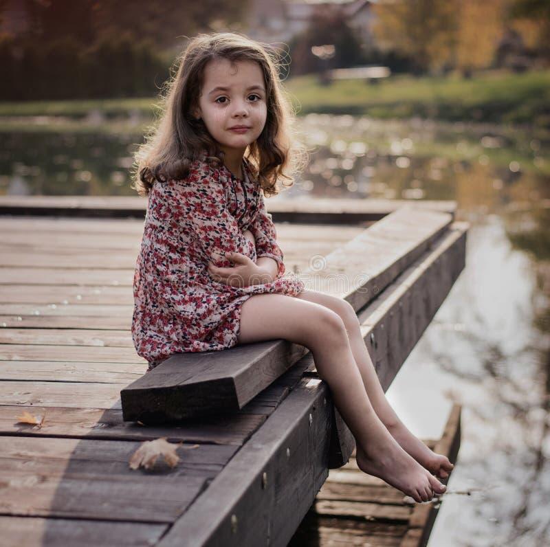 Portret nędzny małej dziewczynki obsiadanie na jetty obraz stock