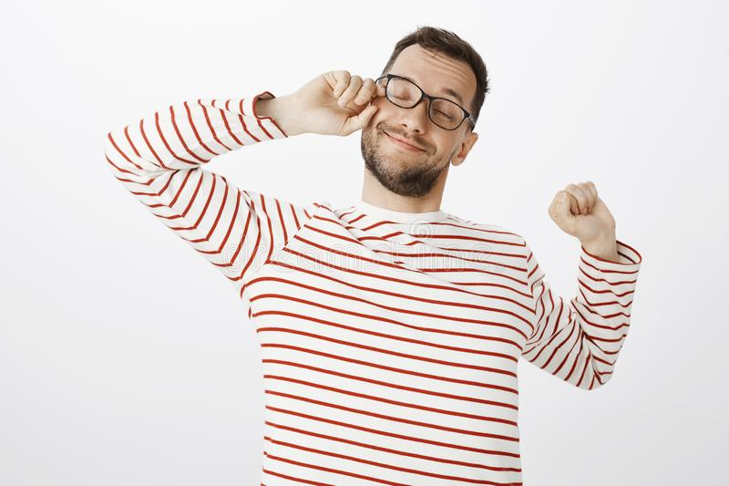 Portret naciera oko i ono uśmiecha się szeroko śpiący zmęczony zadowolony facet w szkłach, podczas gdy rozciągający od skołowania zdjęcia stock