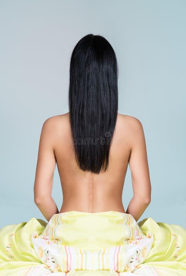 Kobieta z długim czarni włosy obsiadaniem na łóżku obrazy royalty free