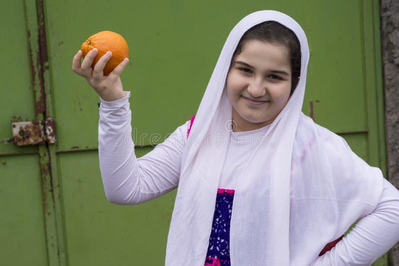 Portret nastoletnia piękna szczęśliwa dziewczyna z pojedynczą pomarańcze zdjęcia stock