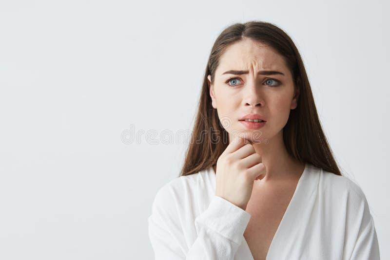 Portret nerwowa młoda brunetki dziewczyna myśleć patrzeć w bocznej mienie ręce na podbródku nad białym tłem zdjęcia stock