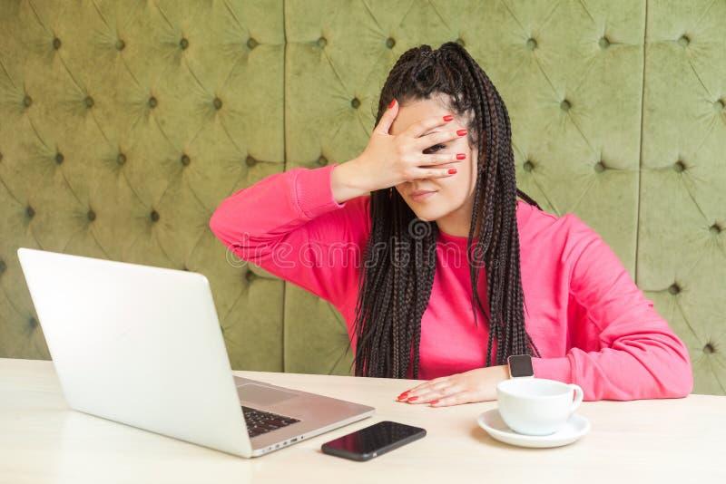 Portret niedowierzania emocjonalnego, młoda kobieta z czarnymi dredami w różowej bluzce siedzi w kawiarni i pokrywa fotografia royalty free