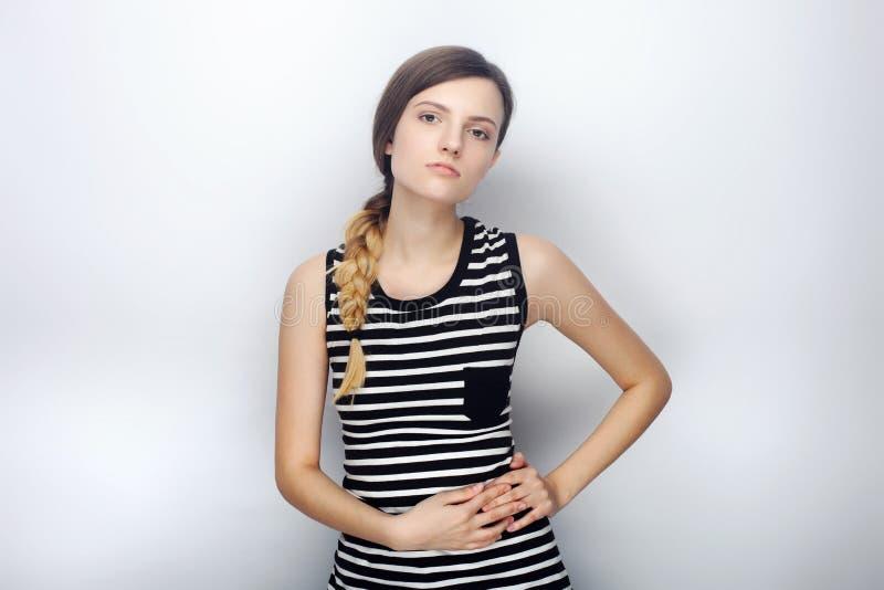 Portret niegrzeczna młoda piękna kobieta w pasiasty koszulowy pogardliwy patrzeć w kamerę pozuje dla wzorcowych testów przeciw st obrazy stock