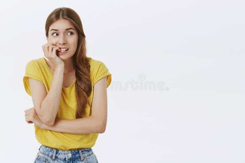 Portret niemądra strasząca śliczna dziewczyna patrzeje prawy z złego przyzwyczajenia gryzieniem dotyka od paniki i niepokoju mars obraz royalty free