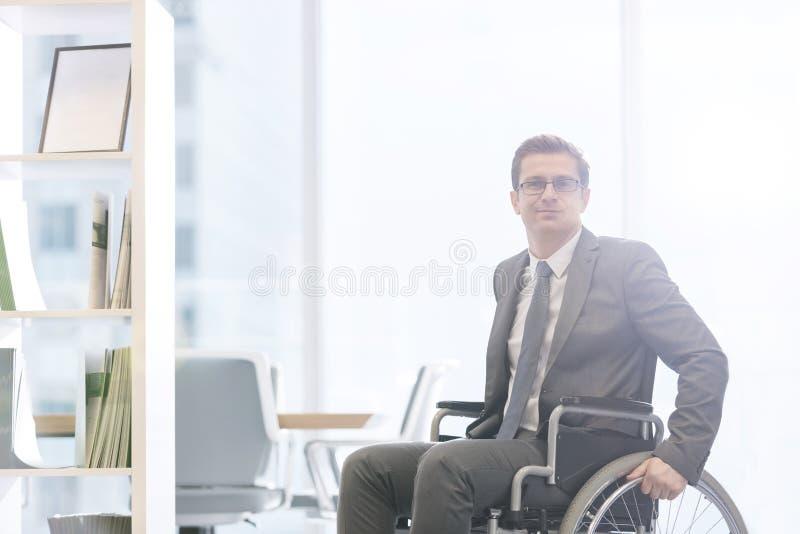 Portret niepełnosprawny biznesmen na wózku inwalidzkim przy nowożytnym biurem fotografia stock