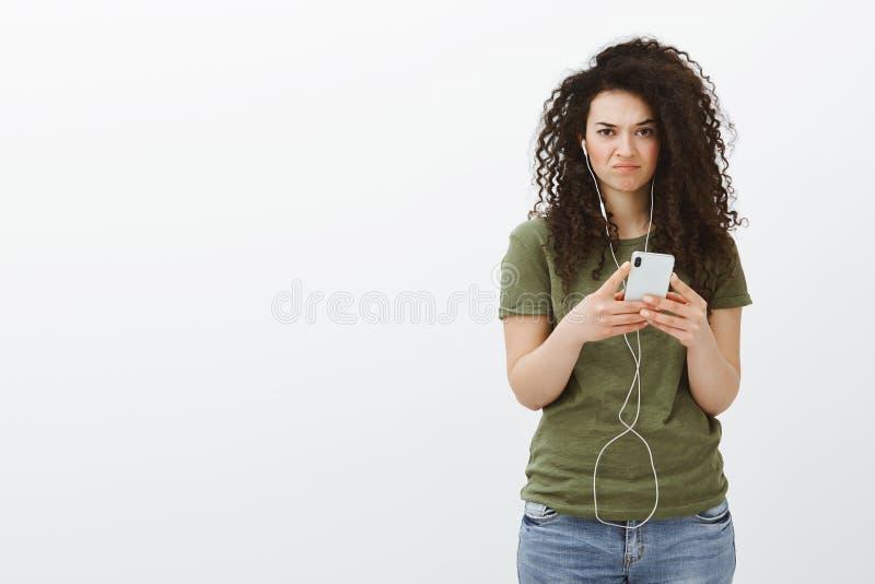 Portret nieporuszony nierad atrakcyjny żeński uczeń z kędzierzawym brown włosy, trzyma smartphone i być ubranym zdjęcie stock