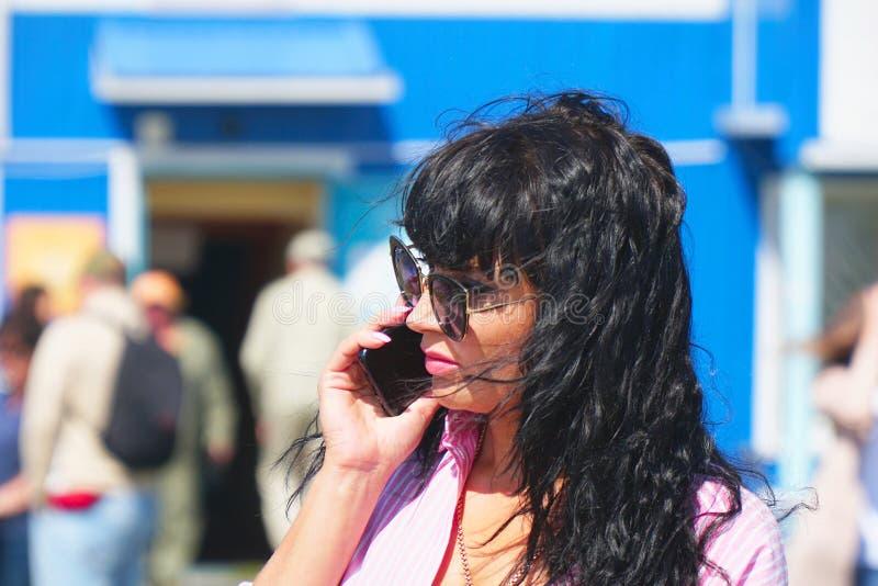 Portret nieprzyzwyczajona brunetki kobieta opowiada na telefonie w okularach przeciwsłonecznych obraz stock