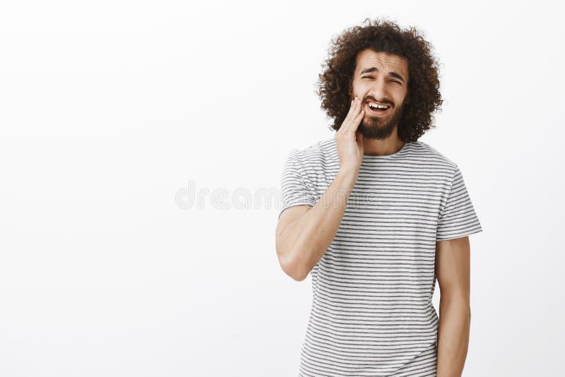 Portret nierad przeszkadzający przystojny Wschodni męski uczeń z afro fryzurą w pasiastej koszulce, wzruszająca broda i zdjęcie royalty free
