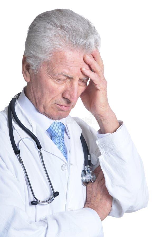 Portret nieszczęśliwa starsza samiec lekarka z stetoskopem odizolowywającym na białym tle zdjęcia stock