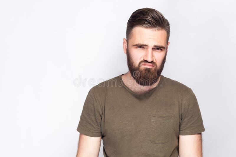 Portret nieszczęśliwy smutny brodaty mężczyzna z ciemnozieloną t koszula przeciw światłu - szary tło zdjęcia stock