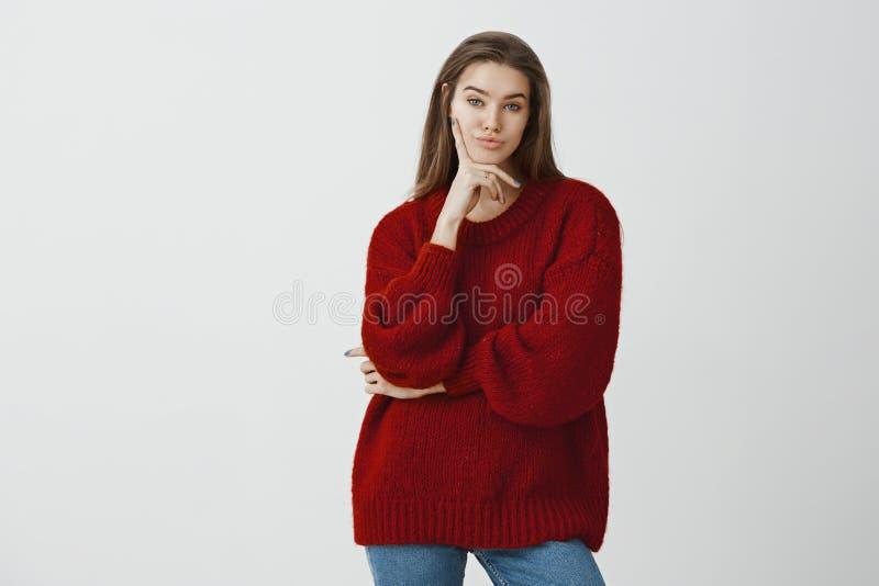 Portret nieszezególna nieporuszona atrakcyjna kobieca europejska kobieta w eleganckim luźnym pulowerze, trzyma dotyka dalej zdjęcia stock