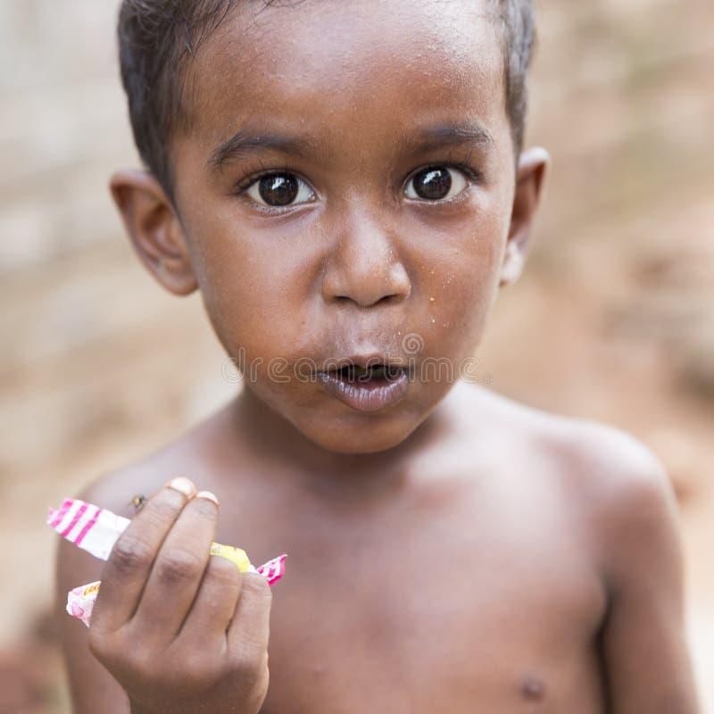 Portret niezidentyfikowana biedna indyjska chłopiec je jego przekąska w ulicie obraz royalty free