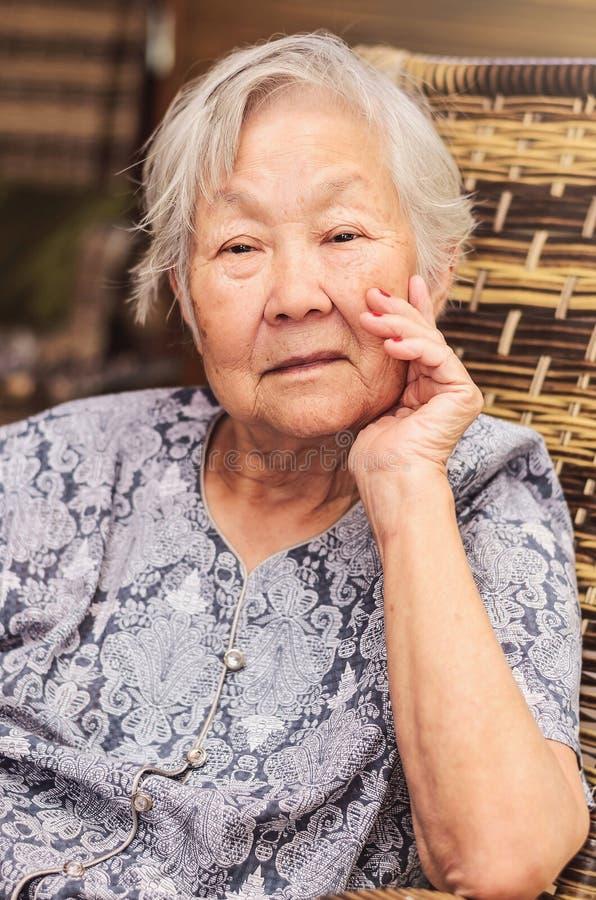 Portret obaasan babcia sadzająca, pozuje z ręką dalej fotografia stock
