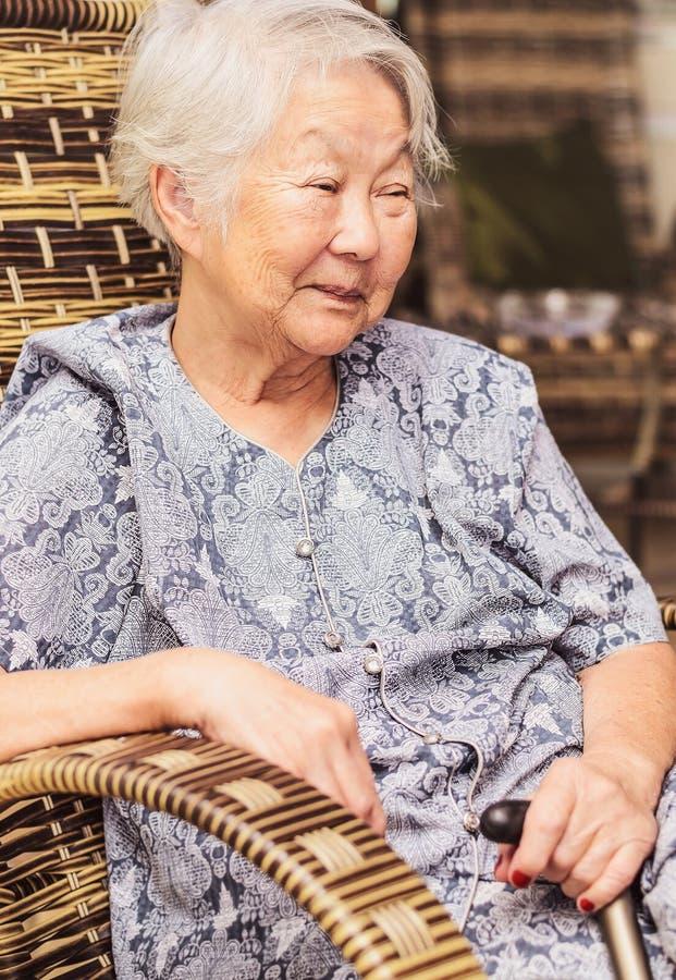 Portret obaasan babcia sadzająca w domu, trzyma walkin obrazy stock