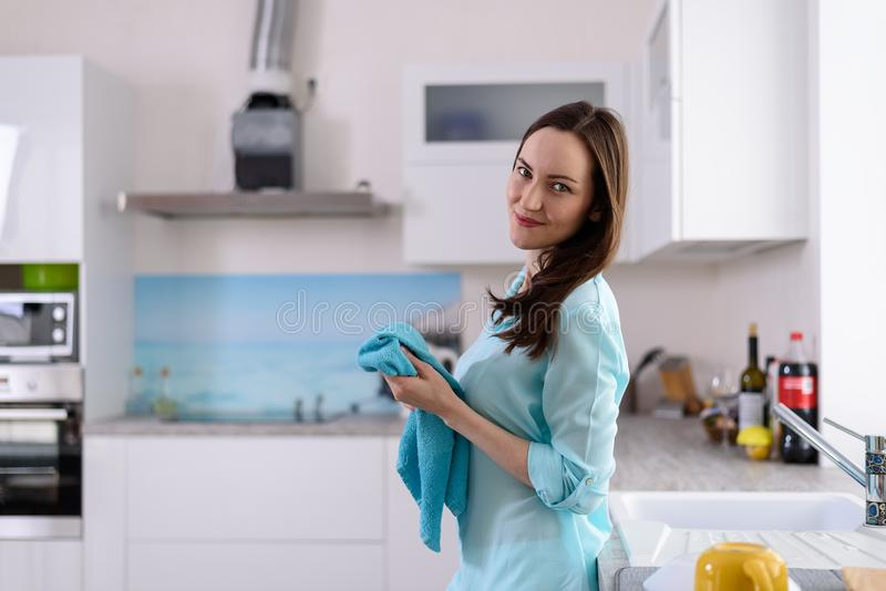 Portret od strony młoda brunetka z naczynie ręcznikiem w jej rękach we wnętrzu jaskrawej kuchni obrazy royalty free