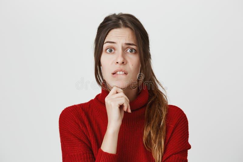 Portret odizolowywający młoda śliczna dziewczyna z brown włosy który patrzeje zmartwionego gryzienie jej wargi i mienia ręka na p obraz royalty free