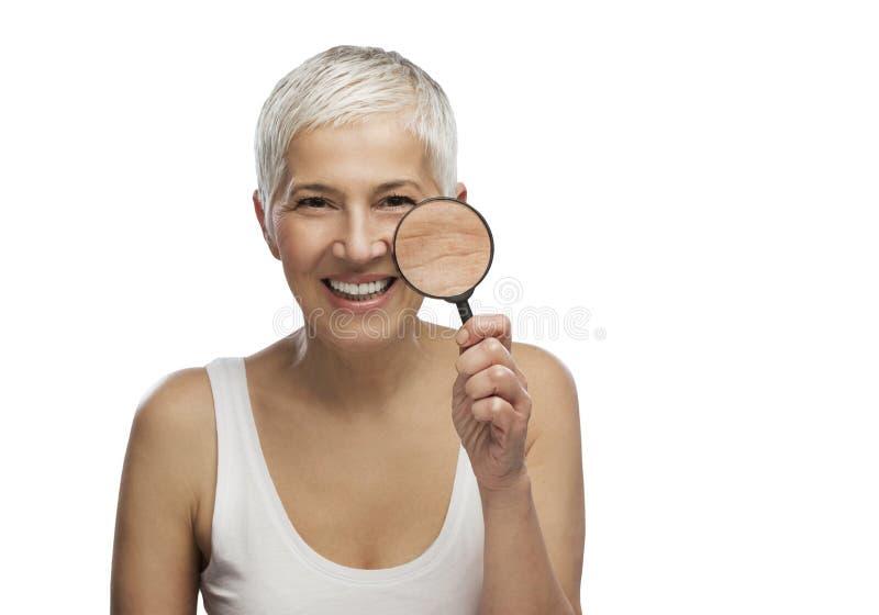 Portret odizolowywający piękna starsza kobieta trzyma powiększać - szkło, obrazy stock