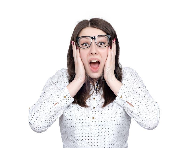 Portret odosobniony na białym tle szokująca młoda dziewczyna w szkłach w horroru mienia rękach za ona twarz, Zgłębia strachu conc zdjęcie royalty free