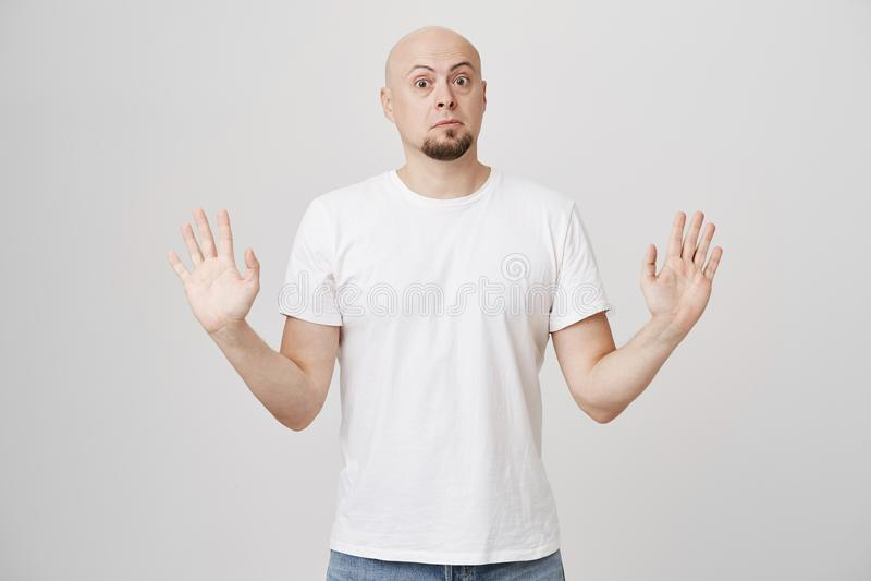 Portret ogłuszone niespokojne łyse caucasian brodate mężczyzna dźwigania ręki w poddaniu gestykuluje, patrzejący z strzelającymi  obraz royalty free