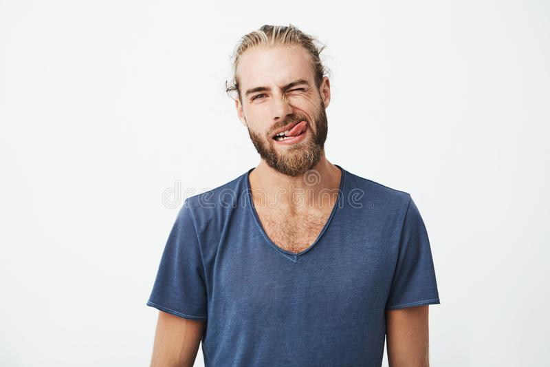 Portret og mooie jonge mens met modieus haar en baard die grappige en dwaze gezichten maken terwijl zijn meisje aan probeert royalty-vrije stock afbeeldingen