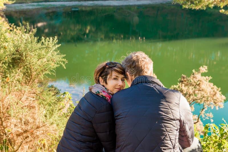 Portret ogląda in camera z pobliskim obsiadaniem jej kochanka młoda kobieta Pary przytulenie i relaksujący pobliski lasowy jezior fotografia royalty free