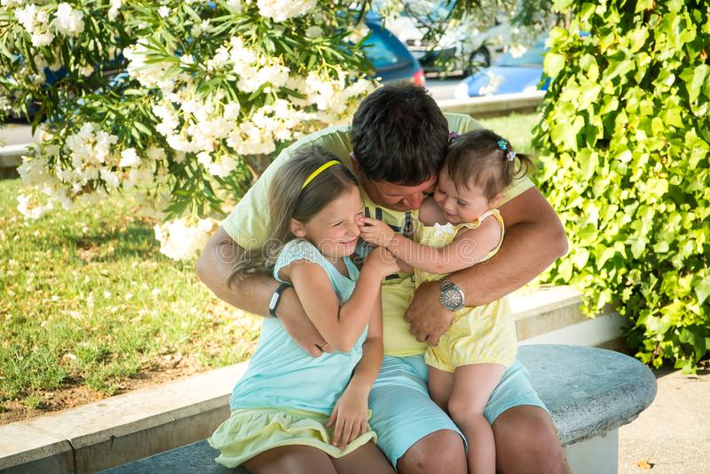 Portret ojciec i dwa małej córki w lato parku zdjęcia royalty free