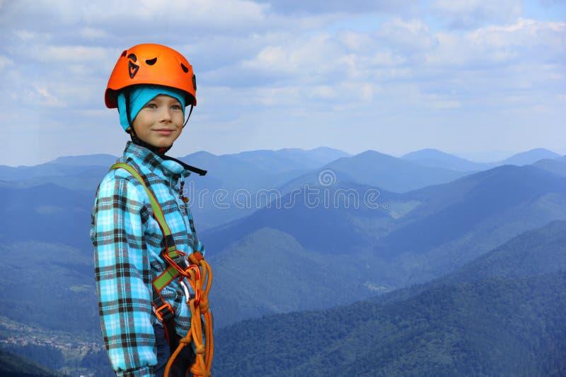Portret ono uśmiecha się sześć roczniaków chłopiec jest ubranym hełma i pięcia zbawczą nicielnicę w górach fotografia stock