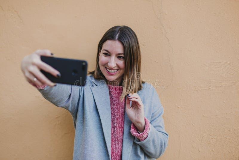 Portret in openlucht van een jonge mooie vrouw met modieuze kleren die over gele achtergrond stellen en een beeld met mobiel neme royalty-vrije stock foto
