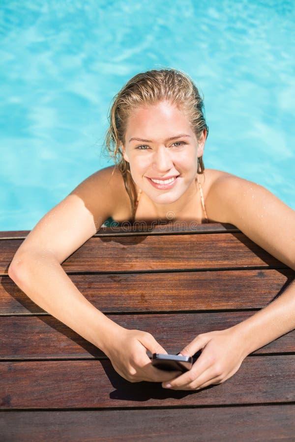 Portret opiera na poolside i pisać na maszynie wiadomość tekstową piękna kobieta obrazy stock