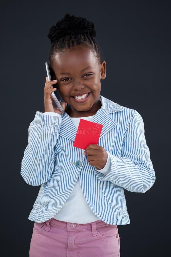 Portret opowiada na telefonie rozochocony bizneswoman podczas gdy trzymający czerwoną kartkę zdjęcia royalty free