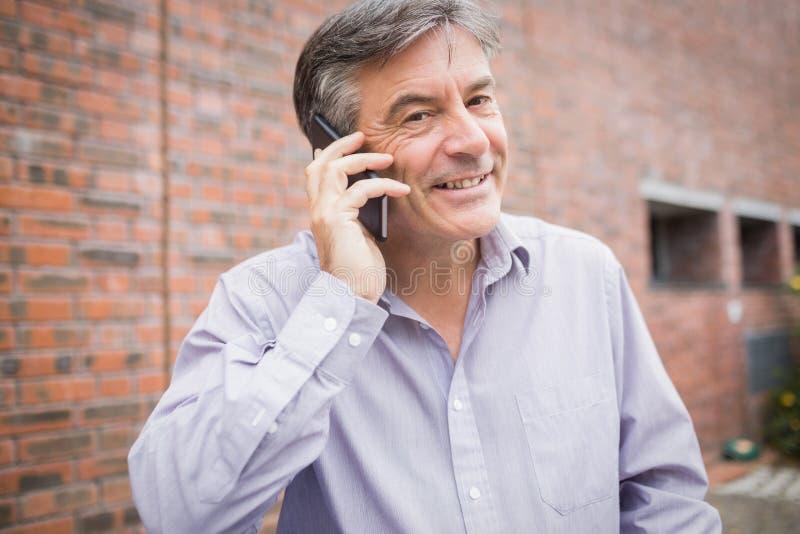 Portret opowiada na telefonie szczęśliwy profesor zdjęcie royalty free