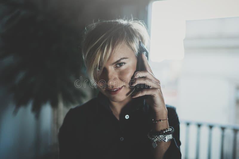 Portret opowiada z partnerem na smartphone przyrządzie uśmiechnięty bizneswoman podczas gdy pracujący daleko w biznesowej podróży fotografia royalty free