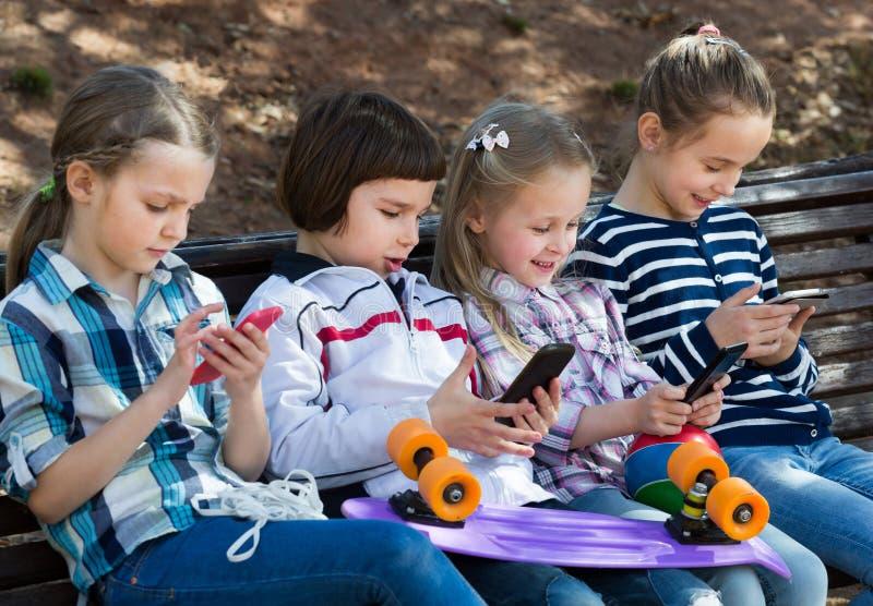 Portret ordynariuszów dzieciaki bawić się z telefonami zdjęcie royalty free
