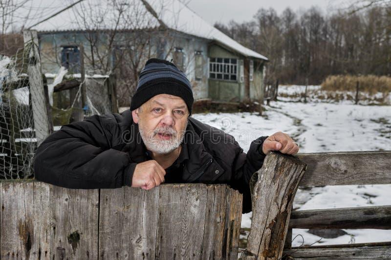 Portret osamotniony Ukraiński stary człowiek z łzawą twarzy pozycją przy jego płotowym blisko zaniedbywającym domem w wiejskiej U zdjęcia royalty free
