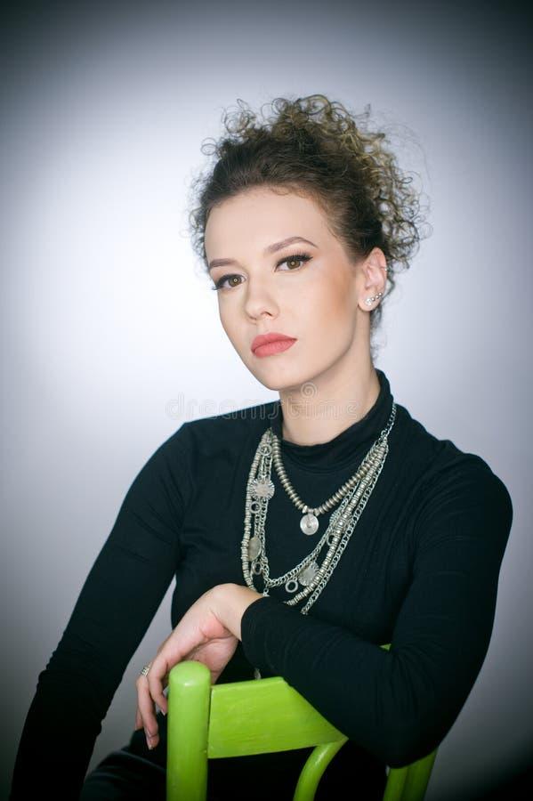 Portret oszałamiająco modny wzorcowy obsiadanie w zielonym krześle, studio strzał Zamyka w górę portreta młoda piękna kobieta zdjęcie stock