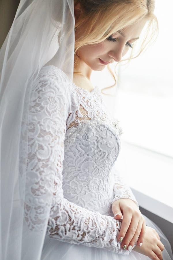 Portret panna młoda w modnym białym ślubnej sukni narządzaniu dla ślubnej ceremonii Portret blondynki kobieta blisko okno zdjęcia stock