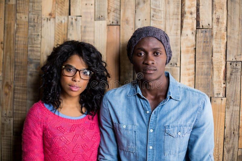 Portret pary pozycja przeciw drewnianej ścianie fotografia stock