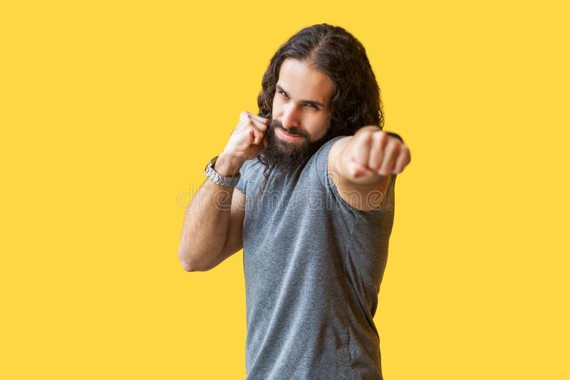 Portret patrzeje i uderza pięścią przy gniewny silny brodaty młody człowiek z długim kędzierzawym włosy w popielatej tshirt pozyc zdjęcie royalty free