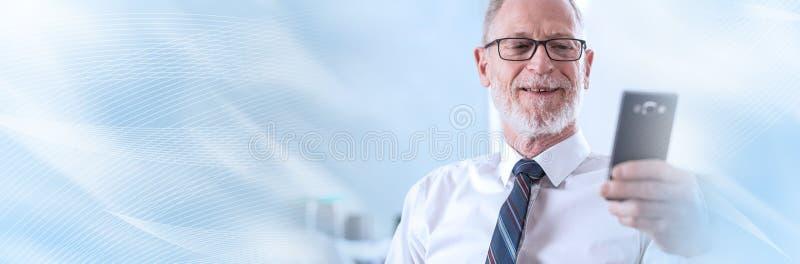 Portret patrzeje jego telefon komórkowego starszy biznesmen; panoramiczny sztandar zdjęcie stock