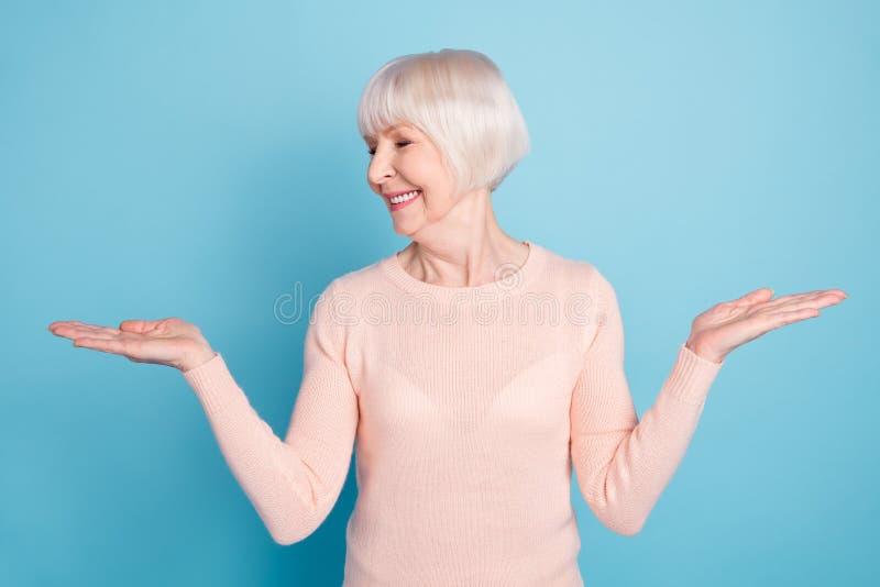 Portret patrzeje jej palmy przedstawia sprzedaże śliczna kobieta pomija być ubranym pastelowego pulower odizolowywającego nad błę obraz stock