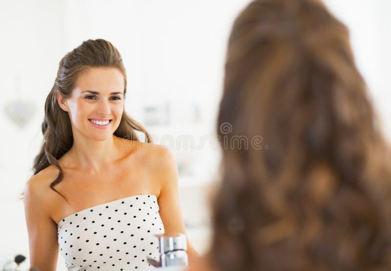 Portret patrzeje w lustrze uśmiechnięta młoda kobieta zdjęcia stock