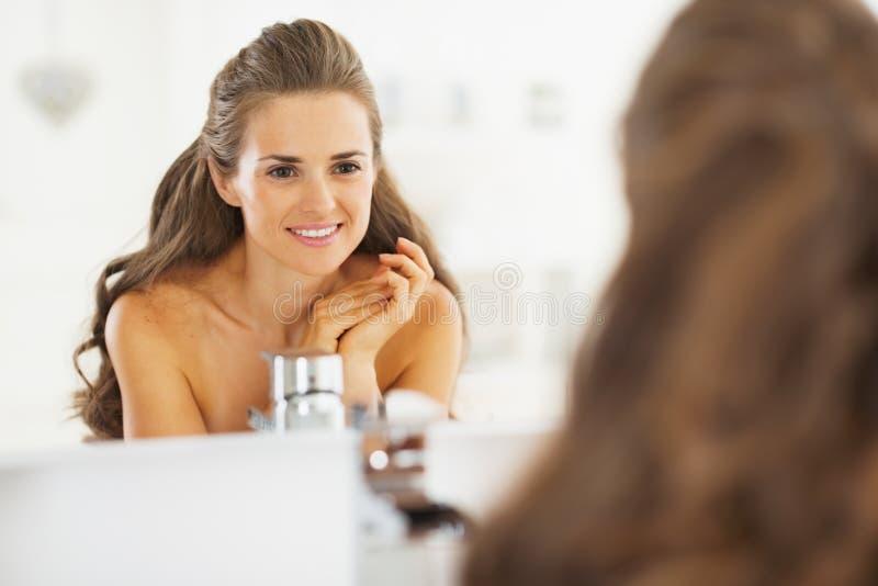 Portret patrzeje w lustrze w łazience szczęśliwa młoda kobieta obrazy stock
