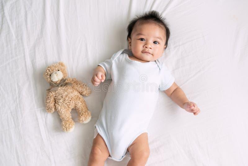 Portret pełzający dziecko na łóżku w jej izbowej, Uroczej chłopiec w białej pogodnej sypialni, Nowonarodzony dziecko relaksuje w  zdjęcia royalty free