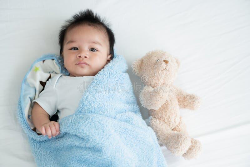 Portret pełzający dziecko na łóżku w jej izbowej, Uroczej chłopiec w białej pogodnej sypialni, Nowonarodzony dziecko relaksuje w  obrazy royalty free