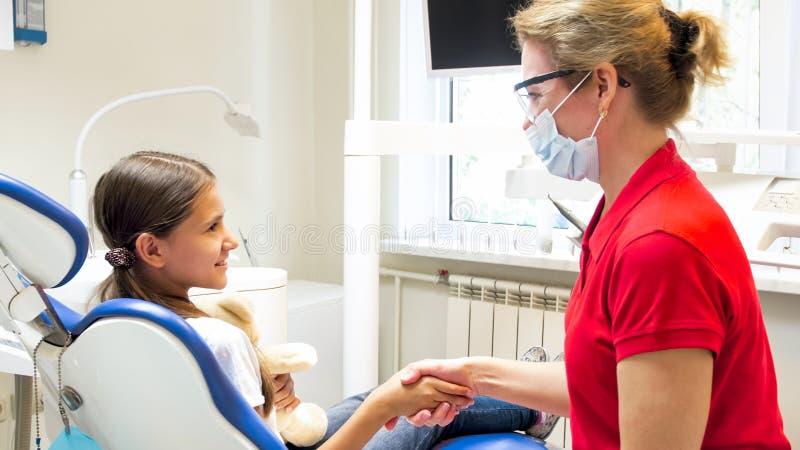Portret pediatrycznego dentysty dziewczyn potrząsalna ręka po taktować zęby obraz stock