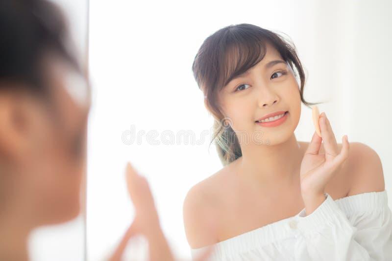 Portret piękna młoda azjatykcia kobieta stosuje prochowego chuch przy policzka makeup kosmetyczny przyglądający lustro fotografia royalty free