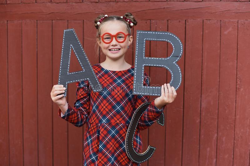 Portret piękna młoda uczennica na czerwonego drewnianego tła witn listów dużym abc Pożegnalny Bell Dzień wiedza zdjęcia stock