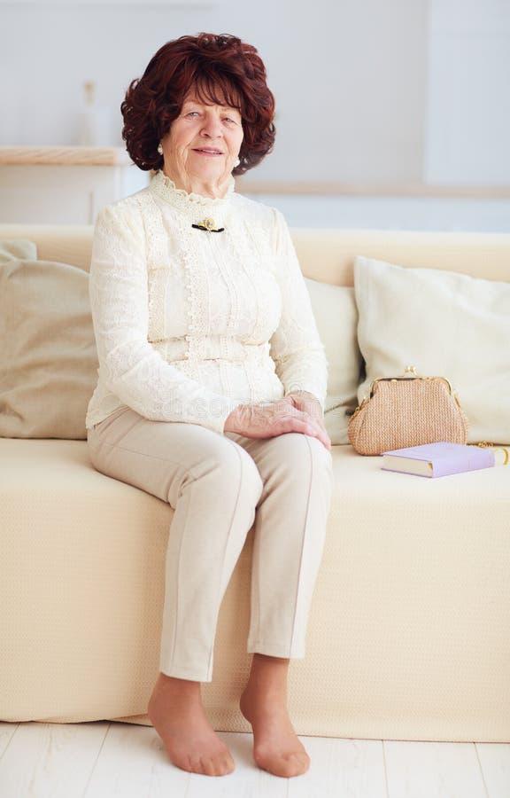 Portret piękny dojrzały kobiety 80 lat siedzi na kanapie w domu obrazy royalty free