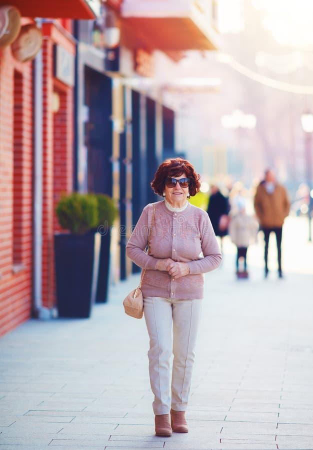 Portret piękny, modny dojrzały kobiety 80 lat chodzi na miasto ulicie, obraz stock