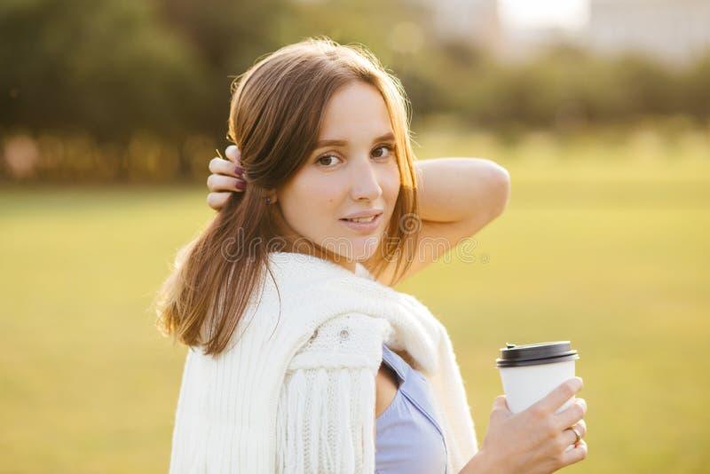Portret piękna ładna kobieta z ciemnym włosy, zdrowa czysta skóra, ubierająca w przypadkowym stroju, pije takeaway kawę, pozuje o fotografia royalty free